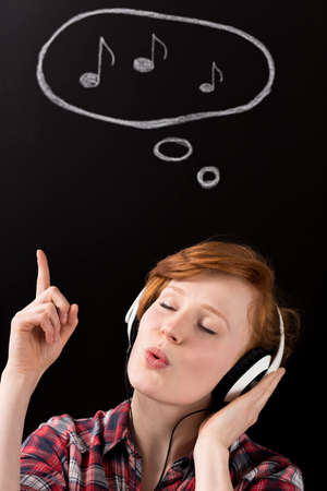 whistling: Young whistling woman in earphones, closed eyes and raised finger