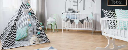 Beautiful baby room with play tent, white cot, cradle and chalkboard, panorama