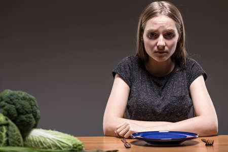 skinny: Mujer repulsivo para que se sienta a la mesa con un plato vacío delante de ella
