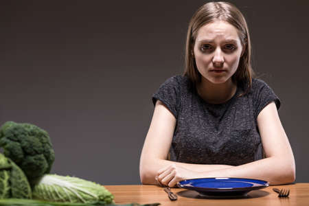 obsessive: Revulsed woman sitting at the table with an empty plate in front of her Stock Photo