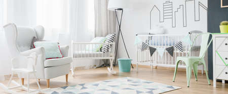 simple girl: Light and spacious baby room with window, armchair, cradle, cot, chair, commode and blackboard, panorama Stock Photo