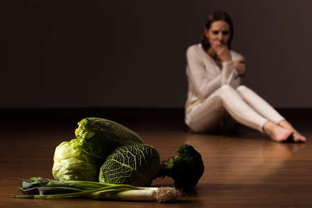 Disgusted woman sitting on the floor and looking at the vegetables