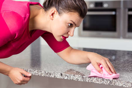 pedant: Concentrated woman with perfect make-up cleaning the kitchen worktop Stock Photo