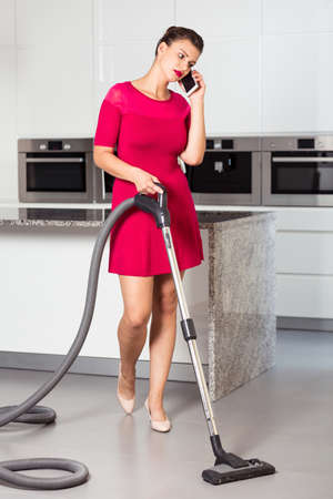 pedant: Woman using the vacuum to dust the floor and talking on the mobile phone