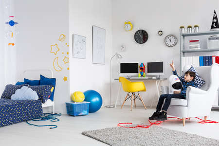 moon chair: Shot of a fully furnished room for a young astronaut with a boy sitting on the armchair Stock Photo