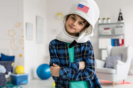 Shot of a boy with astronaut helmet in his room full of cosmic themes
