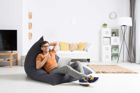 man sit: Young man sitting on a modern bean bag, drinking coffee, watching something on his laptop Stock Photo