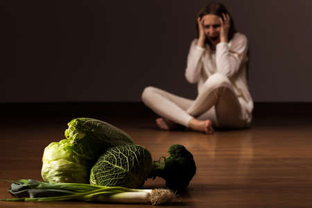 Woman with eating disorder looking at the vegetables and shouting