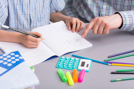 Shot of a desk where a little boy does his homework