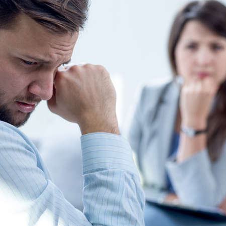 sadness: Resigned man receiving psychotherapy at psychiatrists office