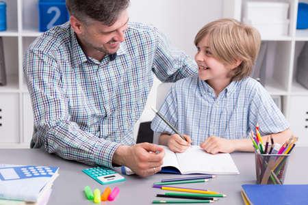 tarea escolar: Disparo de un hombre sonriente ayudando a su pequeño hijo a hacer la tarea Foto de archivo