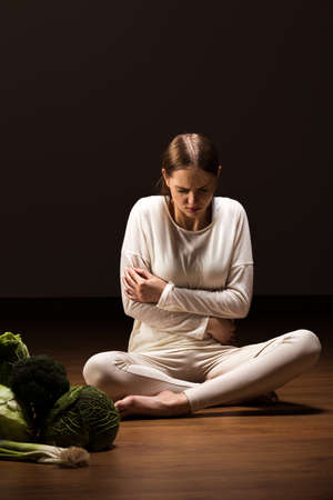 White dressed woman embracing herself by her arms with green vegetables on the floor