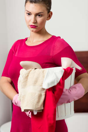 pedant: Bored woman keeping the bin with dirty clothes and towels