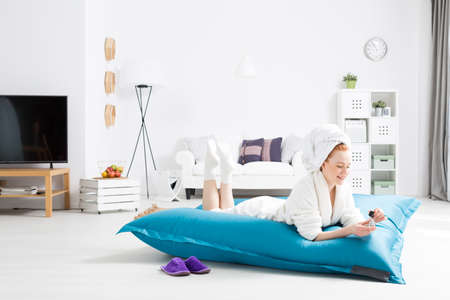 bean bag: Woman wearing robe, with towel on head lying on a bean bag sit in cozy and light home interior Stock Photo