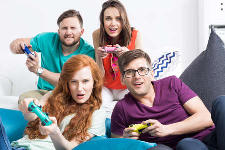 Group of friends playing together video games, sitting on modern poufs, light background