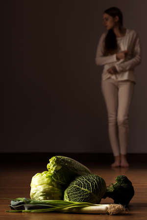 Floor with green vegetables and white dressed woman standing at the backgroung