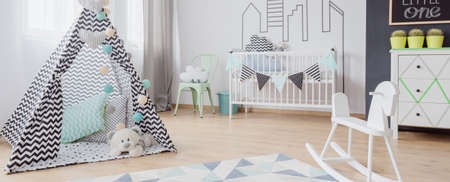 scandinavian people: Light baby room with play tent, simple cot, chalkboard and wooden floor panels, panorama