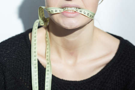 tied down: Closer shot of down half of womans face with the cenitmeter tied around her mouth Stock Photo