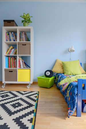 lightsome: Child room with bookstand, bed and carpet with geometric pattern Stock Photo