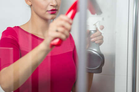 pedant: Pink dressed woman concentrated on cleaning the shower