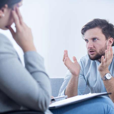 personas enojadas: El hombre enojado hablando con psiquiatra o psicólogo