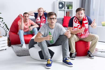cerillos: decepcionado grupo de jóvenes aficionados al fútbol viendo el partido, sentado en pufs modernos