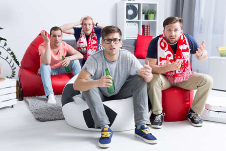 streichholz: Dissapointed Gruppe von jungen Fußballfans beobachten Spiel, auf modernen pufs sitzen