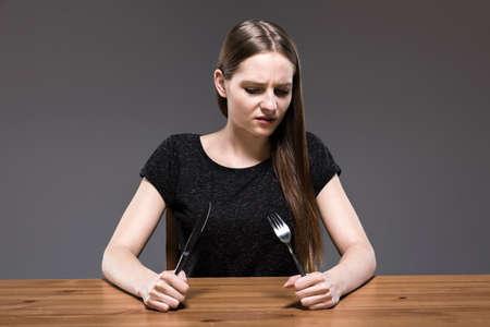 skinny: mujer de pelo largo que mira la cubertería mantuvo en sus manos