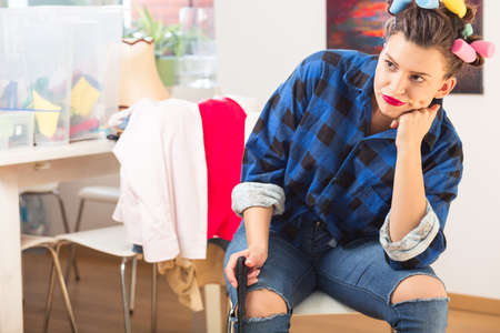 messy room: Woman with curling pins in her hair sitting on a chair in messy room Stock Photo