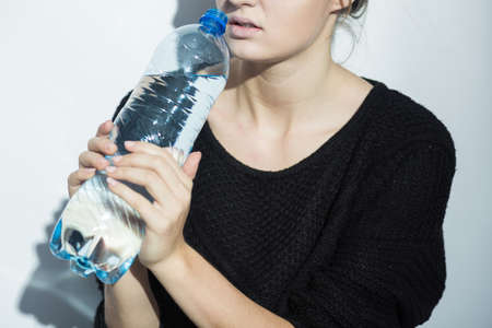 Shot of a woman keeping the bottle of water with both hands