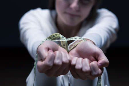 obsessive: Closer shot of womans hands tied by a centimeter Stock Photo