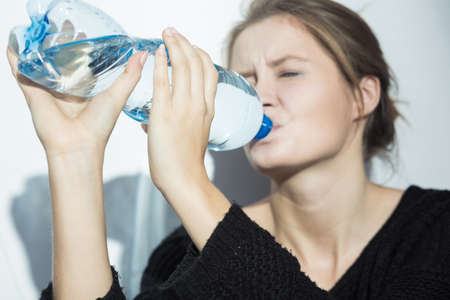 kept: Shot of a woman drinking water from the bottle kept both hands