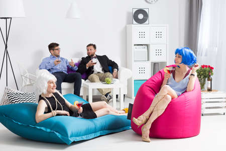 housewarming: Group of friends having home party, two women sitting on modern bean bag sits Stock Photo