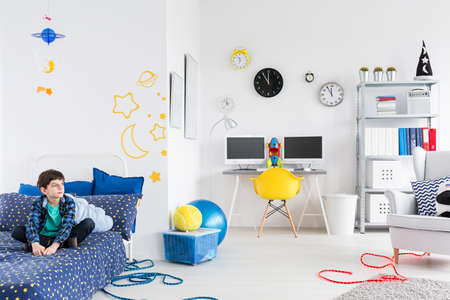 moon chair: Shot of a fully furnished room for a young astronaut with cosmic themes on the wall and with a boy sitting on his bed Stock Photo