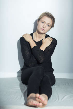 Shot of young woman in black clothes  sitting on the floor with hands on her shoulders