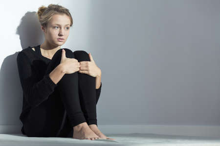 Distressed young woman sitting on the floor, leaned on the wall