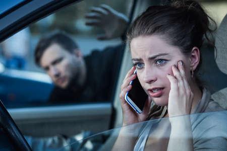 robo de autos: ladrón de coches y una mujer distraída hablando por un teléfono celular