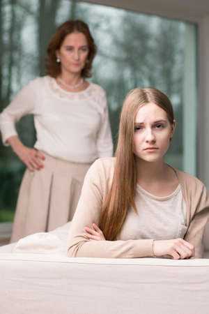 hangup: Strict woman standing behind young woman sitting on a couch Stock Photo
