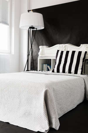 ascetic: Black and white ascetic style bedroom with large bed and floor lamp
