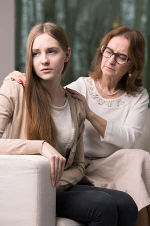 hangup: Woman therapist sitting on a couch behind the young teenager Stock Photo