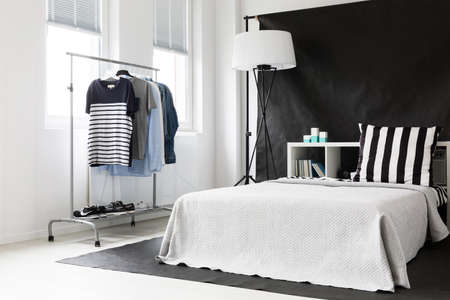 ascetic: Black and white bedroom in ascetic style with window, functional clothes rack and bed Stock Photo