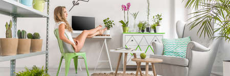 lightsome: Relaxed woman is sitting on a chair with her feet on the desk in room full of flowers Stock Photo