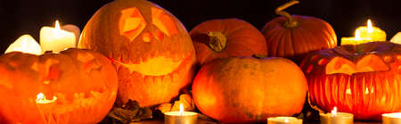 Pumpkins, pumpkin lanterns and candles standing on a dark background, panorama Stock Photo