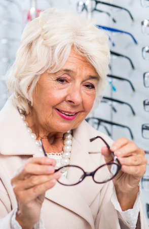 woman shop: Senior woman searching for a new eyeglass frames Stock Photo