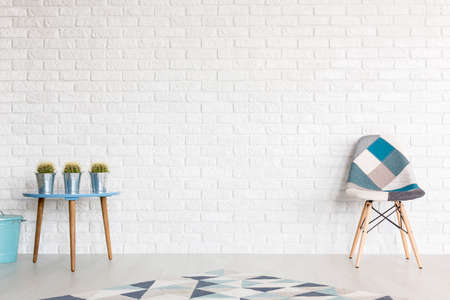 coffee table: Modern patchwork chair and coffee table in blue and grey, in a bright interior with brick wall