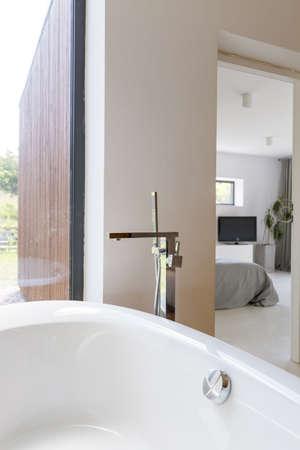 cosy: Modern bathroom with bathtub next to cosy bedroom Stock Photo
