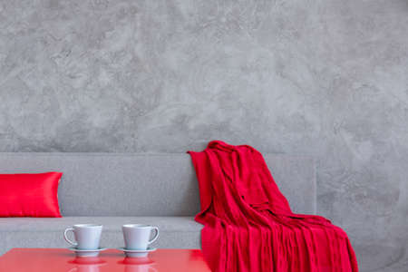 ascetic: Close-up of a red coffee table with two grey cups, in front of a grey sofa in an ascetic interior
