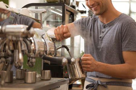 Il lavoratore maschio del caffè sta preparando un latte per un caffè