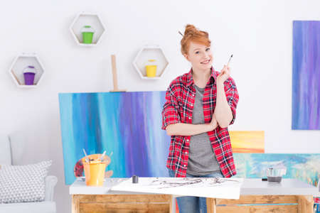 checked shirt: Optimistic young artist in a red checked shirt, holding a brush by a work table in her studio