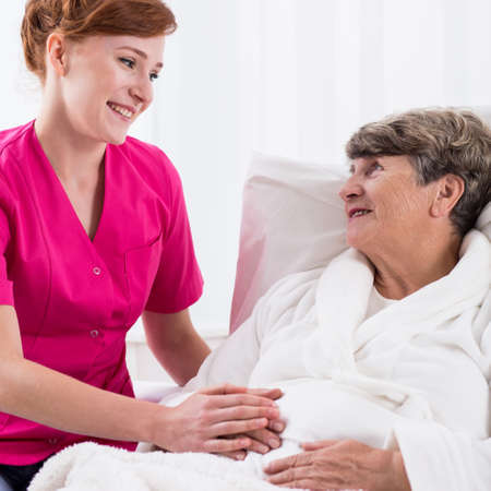 caring for: Young nurse is caring for elderly woman